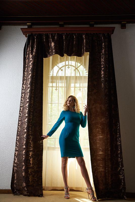 fotomodel in rochie turcoaz langa fereastra