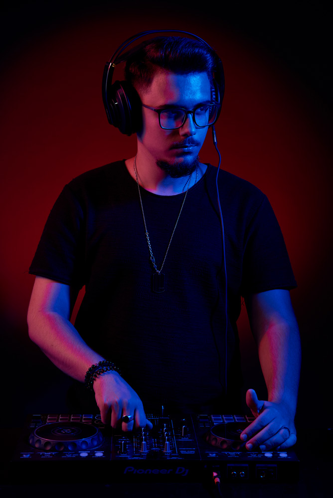 DJ cu casti si consola in lumina de club
