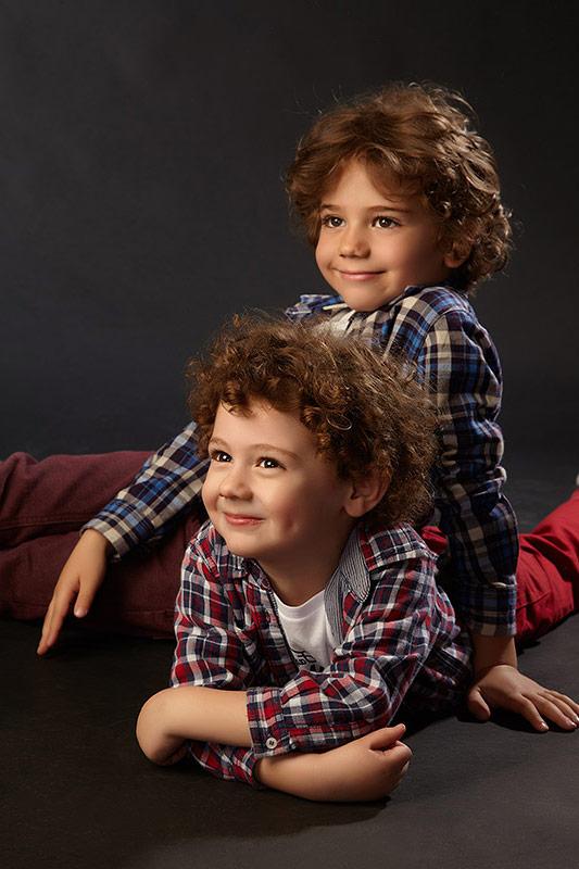 doi copii pozand pe jos la sedinta foto