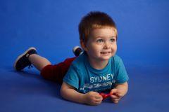 copil in studio pe fundal albastru