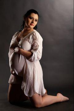 femeie insarcinata in camasa alba in studio
