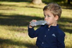 copil cu sticla de apa in parc